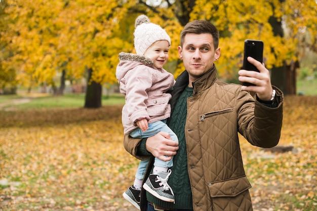 Vater- und kleinkindtochter, die selfie im herbstpark tun
