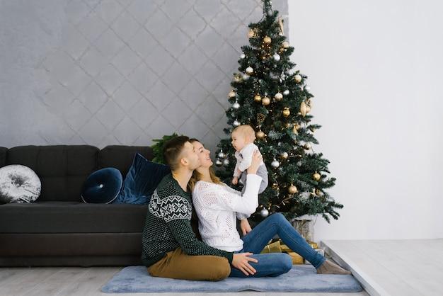 Vater und mutter halten ihren sohn in der nähe eines weihnachtsbaumes