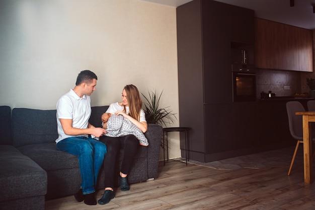 Vater und mutter in einem wohnzimmer mit einem neugeborenen. das erste lebensjahr