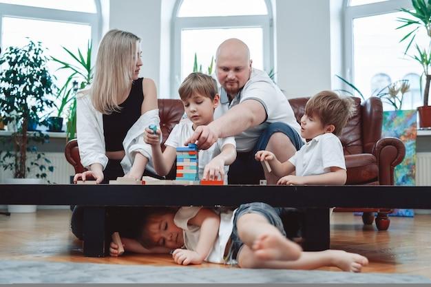 Vater und mutter mit ihren kindern lernen zusammen jenga-spiel zu spielen. porträt von fröhlichen jungen und ihren eltern im wohnzimmer.