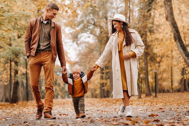 Vater und mutter mit sohn gehen im herbstpark. eine familie geht im goldenen herbst in einem naturpark spazieren.