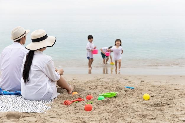 Vater und mutter sitzen am strand und schauen sich die kinder an, die morgens gemeinsam am strand spielzeug auf sand spielen. urlaubs- und reisekonzept.