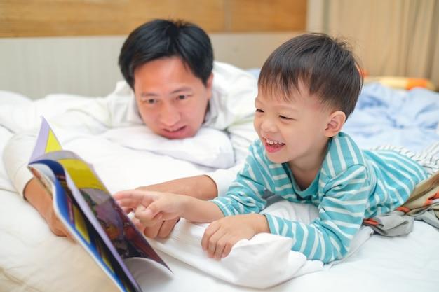 Vater und nettes kleines asiatisches kleinkindjungenkind, die schlafenszeitgeschichtenbuch lesen