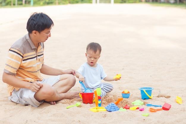 Vater und niedliches kleines asiatisches monate altes kleinkindjungenkind, das amp spielt und strandspielzeug der kinder spielt
