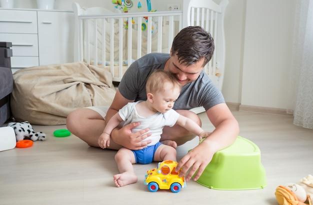 Vater und sein baby spielen mit spielzeugauto auf dem boden zu hause