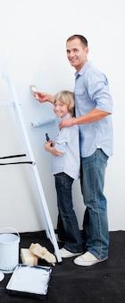 Vater und sein junge, die einen raum mit pinseln malen