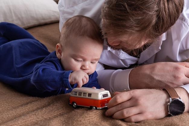 Vater und sein kleiner junge liegen auf dem bett und spielen mit dem minivan-spielzeugauto