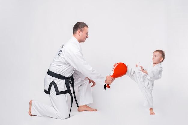 Vater und sein kleiner junge üben taekwondo auf weiß