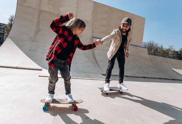 Vater und sein kleiner sohn in freizeitkleidung fahren am sonnigen tag skateboards in einem skatepark mit rutschen draußen.