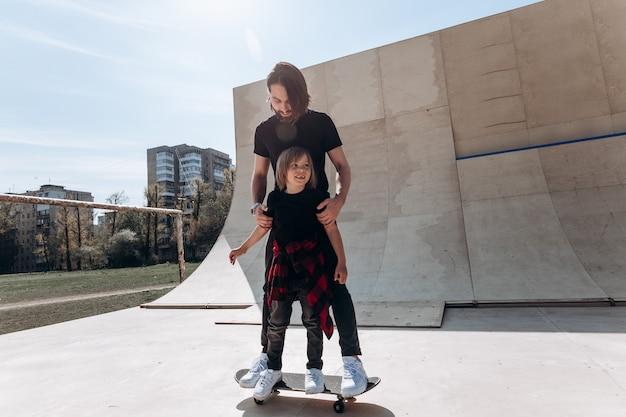 Vater und sein kleiner sohn in freizeitkleidung stehen am sonnigen tag zusammen auf dem einen skateboard in einem skatepark.
