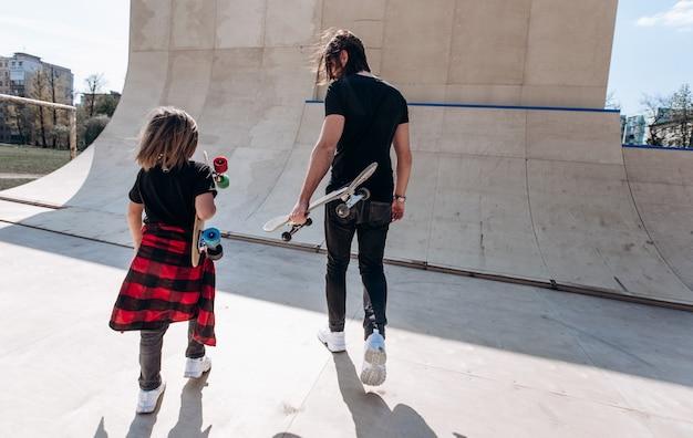 Vater und sein kleiner sohn in stilvoller freizeitkleidung gehen am sonnigen tag mit den skateboards in den händen in einem skatepark.