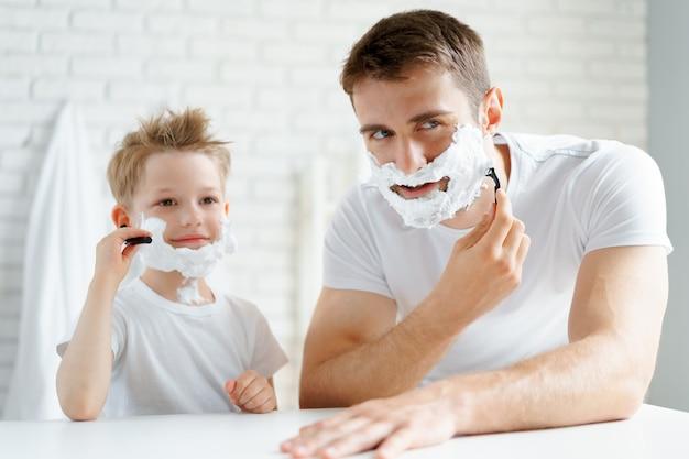 Vater und sein kleiner sohn rasieren sich zusammen im badezimmer