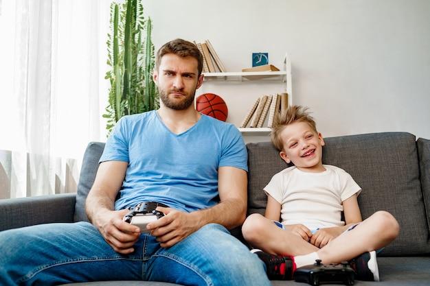Vater und sein kleiner sohn spielen zu hause zusammen videospiele auf der couch