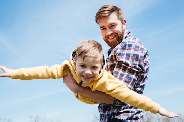 Vater und sein kleiner sohn spielen zusammen in einem park