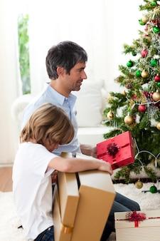 Vater und sein sohn, die weihnachtsgeschenke öffnen