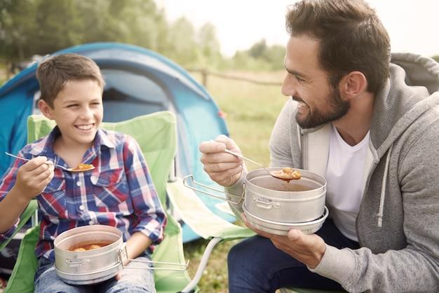 Vater und sein sohn essen auf dem campingplatz zu abend