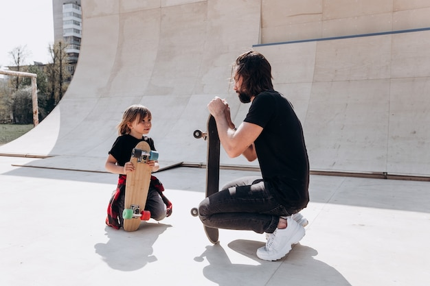 Vater und sein sohn in freizeitkleidung sitzen am sonnigen tag neben den skateboards in einem skatepark.