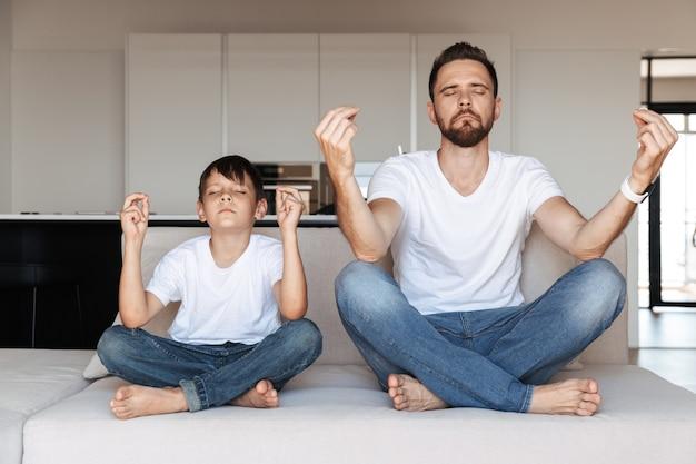 Vater und sein sohn meditieren zusammen auf einer couch