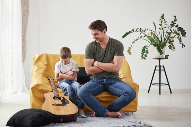 Vater und sein sohn sitzen zusammen auf dem sofa. akustikgitarre auf dem bett.