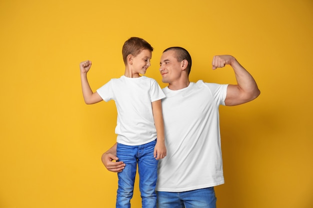 Vater und sein sohn zeigen muskeln an der farbwand