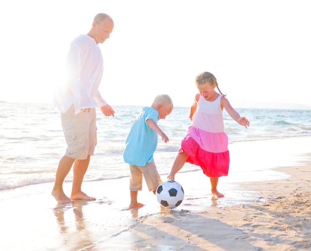 Vater und seine kinder, die zusammen fußball spielen.