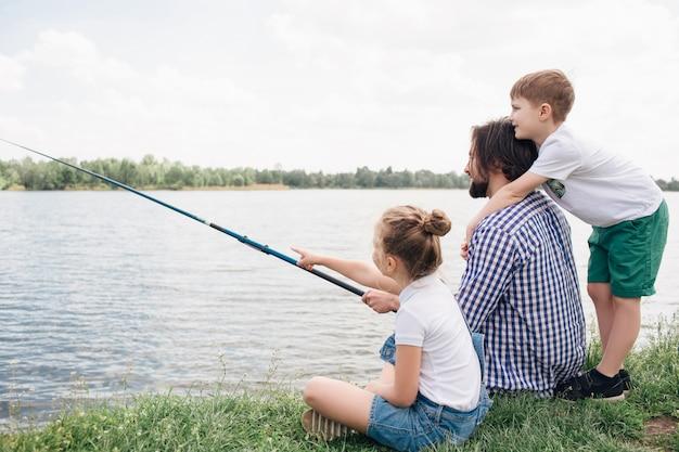 Vater und seine kinder verbringen zeit zusammen am flussufer. sie versuchen, fische zu fangen. mann hält fischrute in händen. junge steht hinter ihm und umarmt. mädchen zeigt nach vorne.