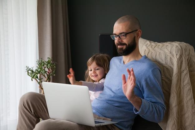 Vater und seine kleine tochter sprechen online mit ihren verwandten