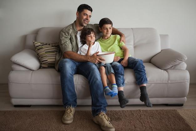 Vater und söhne mit der popcornschüssel, die fernsieht im wohnzimmer