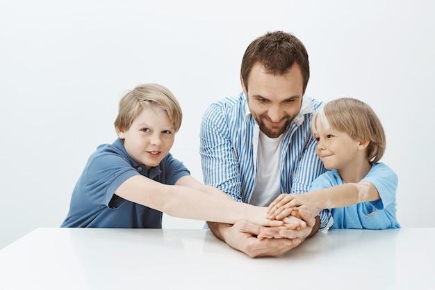 Vater und söhne nicht nur familie, sondern auch team. porträt der glücklichen gutaussehenden geschwister und des vaters, die hände halten, während sie am tisch sitzen und breit lächeln