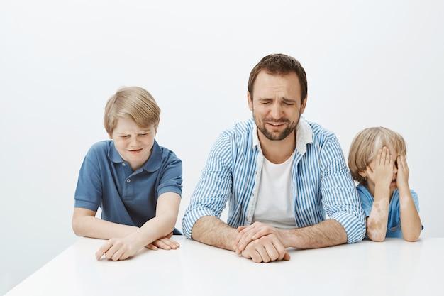 Vater und söhne sind verärgert, während mama bei der arbeit ist. porträt der hungrigen unzufriedenen europäischen familie der männlichen jungen und des vaters, die am tisch sitzen und weinen
