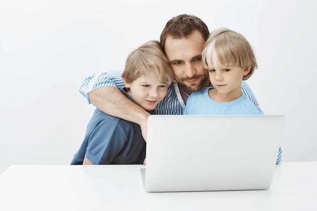Vater und söhne sprechen mit mama per video-chat im laptop. porträt des schönen glücklichen vaters und der jungen, die den notizbuchbildschirm umarmen und betrachten, berührende videos oder niedliche fotos ansehen