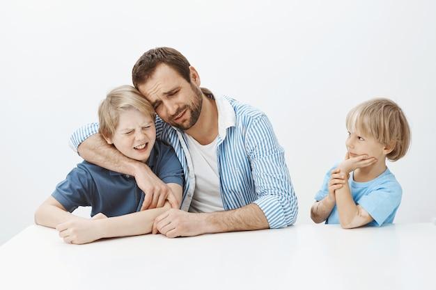 Vater und söhne verstecken ein unangenehmes geheimnis vor einem jüngeren jungen. porträt des düsteren unglücklichen vaters und des kindes, die umarmen und weinen