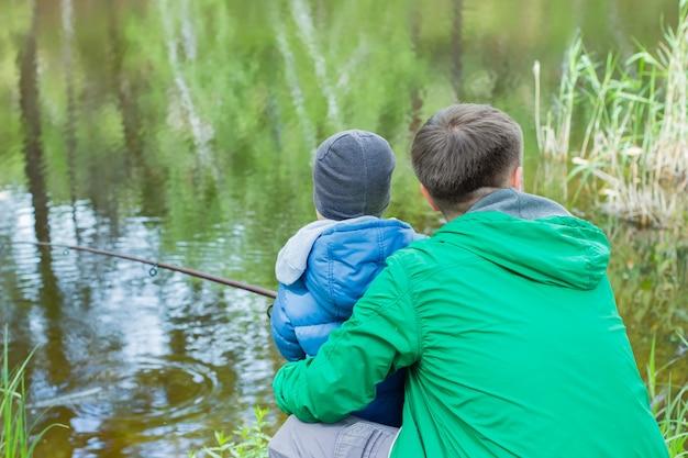 Vater und sohn am flussufer angeln