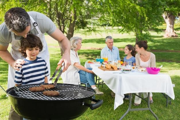 Vater und sohn am grill grillen mit der familie, die im park zu mittag isst