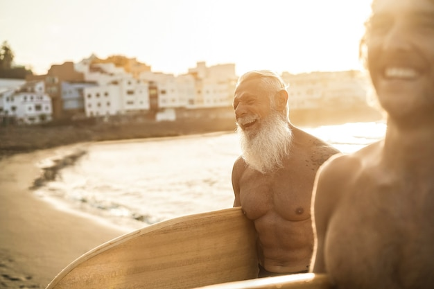 Vater und sohn amüsieren sich nach der surfsession am strand
