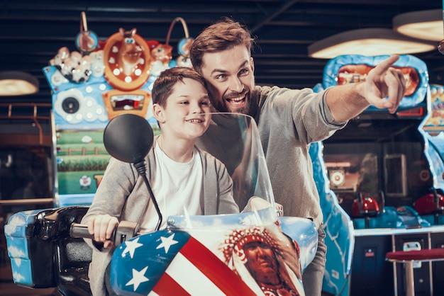 Vater und sohn auf spielzeugmotorrad. familienerholung