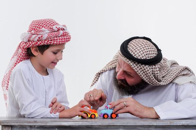 Vater und sohn aus dem nahen osten spielen mit spielzeugauto