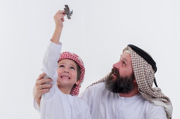 Vater und sohn aus dem nahen osten spielen mit spielzeugflugzeug