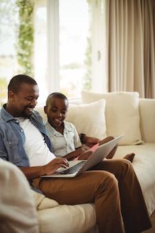 Vater und sohn benutzen laptop im wohnzimmer
