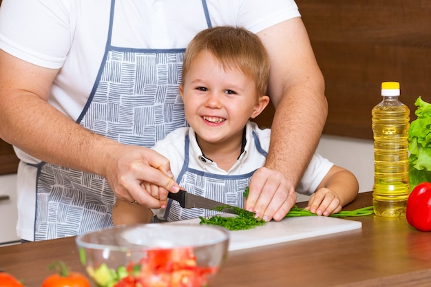 Vater und sohn bereiten salat in der küche mit gemüse zu
