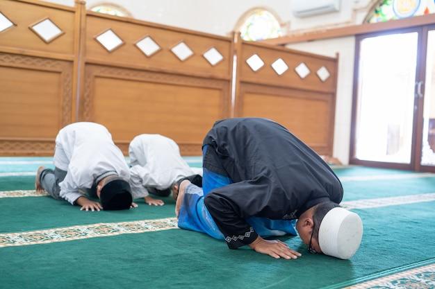 Vater und sohn beten zusammen in der moschee