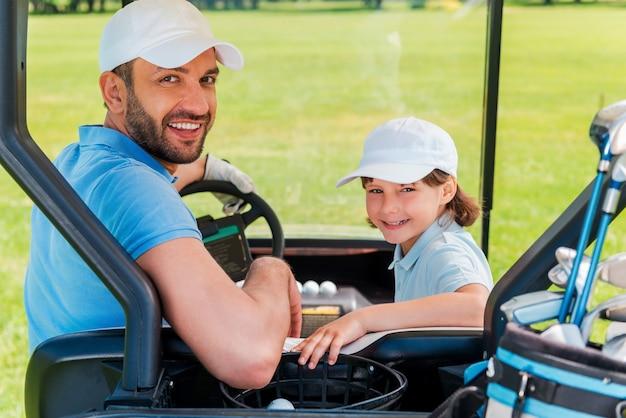 Vater und sohn ? das beste team. fröhlicher junger mann und sein sohn, der beim sitzen im golfwagen in die kamera schaut