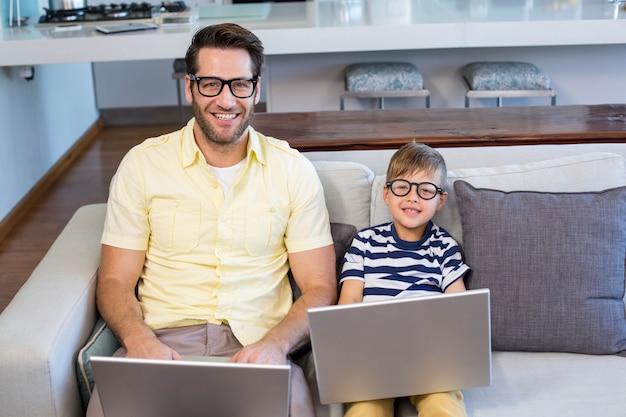 Vater und sohn, der laptope auf der couch verwendet