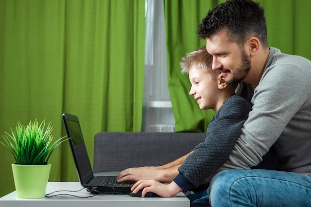 Vater und sohn, die an einem laptop arbeiten.