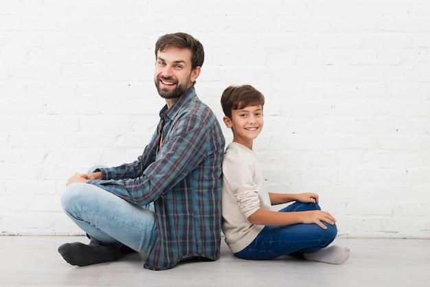Vater und sohn, die auf boden sitzen und fotografen betrachten