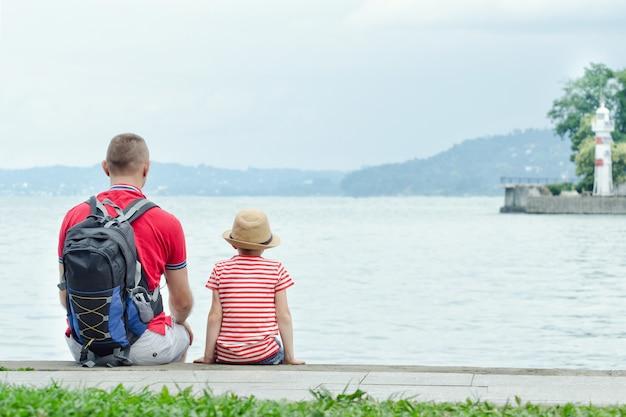 Vater und sohn, die auf dem pier auf dem seehintergrund, dem leuchtturm und den bergen im abstand sitzen. rückansicht