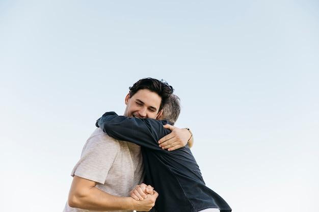 Vater und sohn, die auf himmelhintergrund umarmen