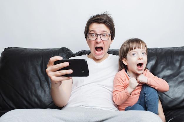 Vater und sohn, die ein furchtsames video am telefon aufpassen