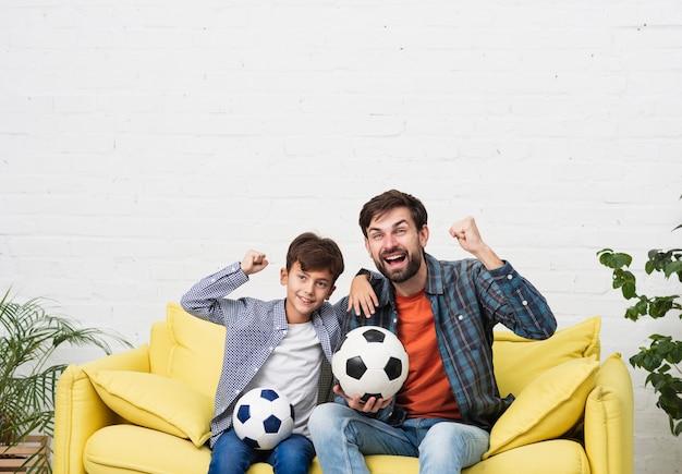 Vater und sohn, die ein fußballspiel aufpassen