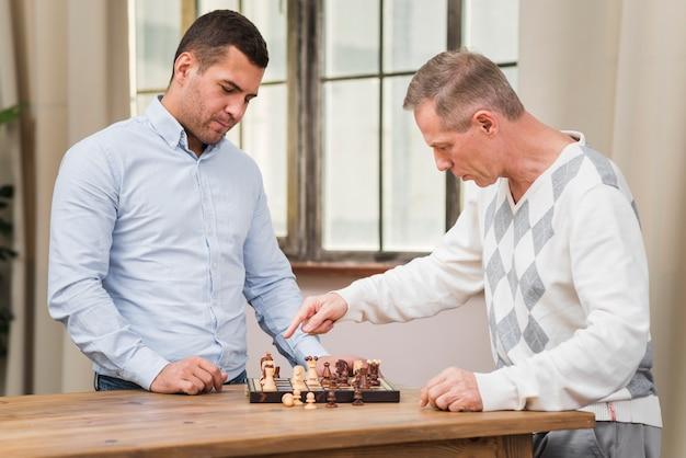 Vater und sohn, die ein schachmatch spielen